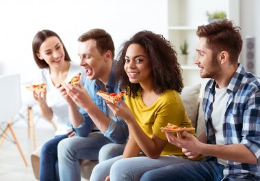 Cheerful friends eating pizza