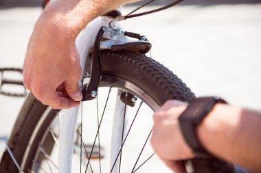 Man checking a wheel on his bike