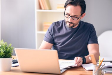 Man holding newspaper in front of laptop