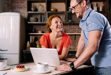 Woman and man standing over laptop