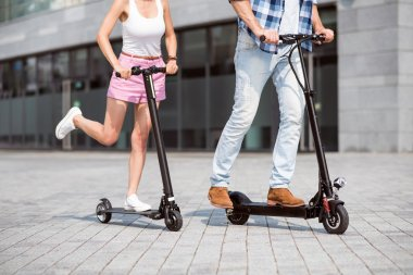 Pleasant friends using scooters
