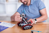Photo Male making cute small robot on the table