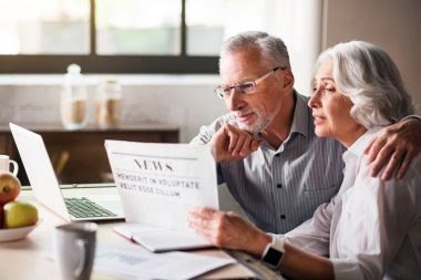 Happy and caring old couple reading newspaper at the kitchen