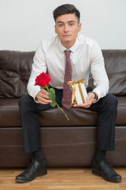 Businessman holding a flower and a present