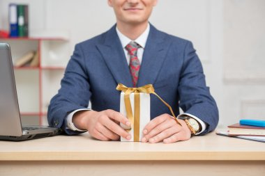 Businessman in office with present box