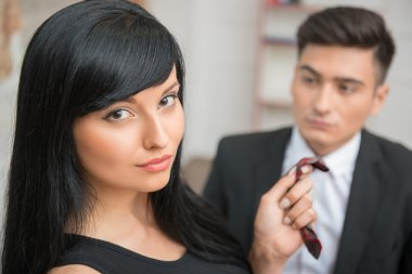 Businesswoman flirting and pulling her colleague by the tie