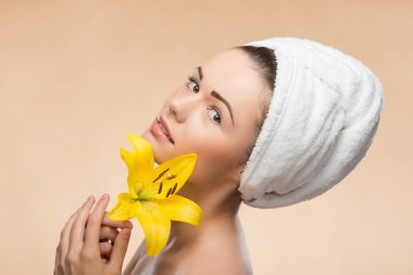 Portrait of girl with clean and  fresh skin with a towel on her head in spa, holding in her hands yellow flower, isolated on beige background stock vector