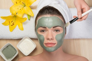 Girl applying facial cream mask