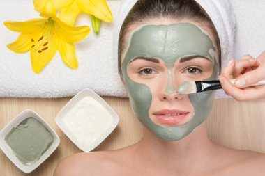 Girl applying facial cream mask