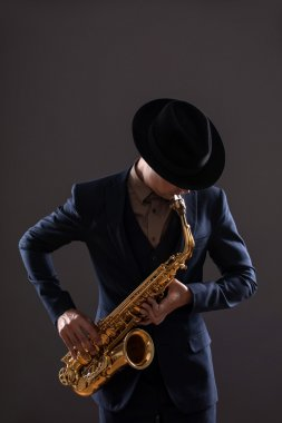 Portrait of a jazz man in a suit with a hat hiding his face and