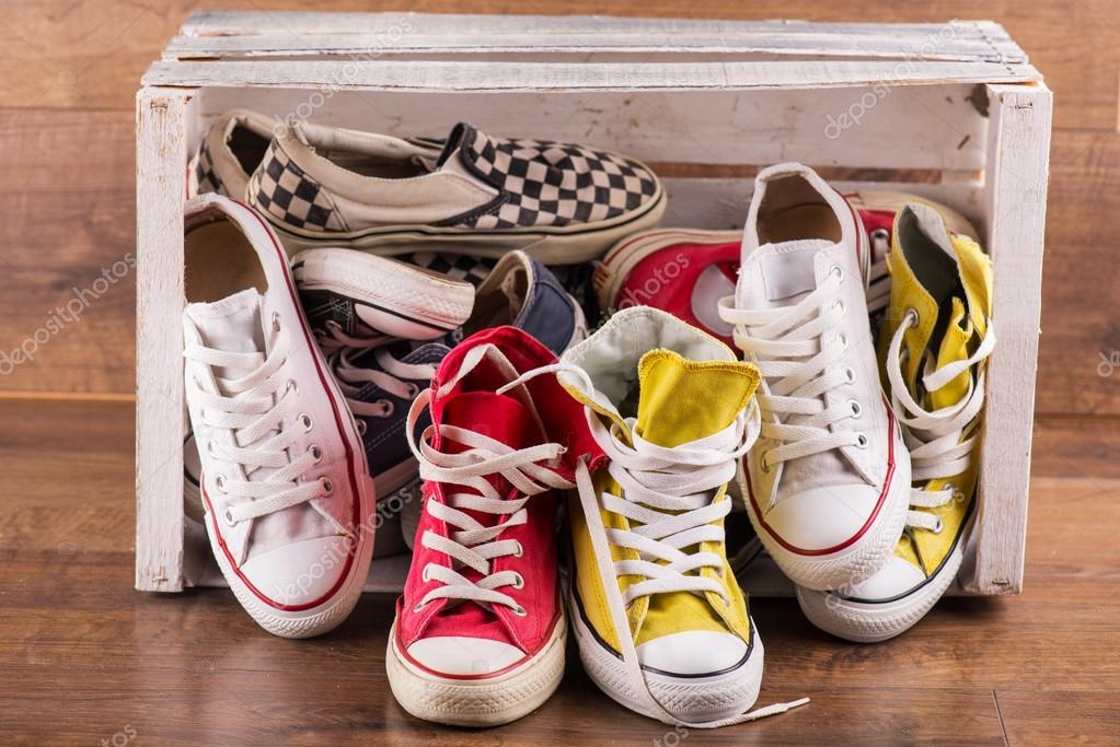 c1e69da51f0 Διάφορα ζευγάρια των δροσερό νεολαίας κόκκινο μπλε παπούτσια λευκό κίτρινο  γυμναστήριο πέσει έξω κουτί λευκό σε καφετί ξύλινο πάτωμα — Εικόνα από  Dmyrto_Z