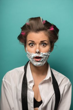 Woman in hair curlers  with foam on face