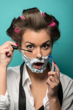 Woman in  foam on her face  applying mascara