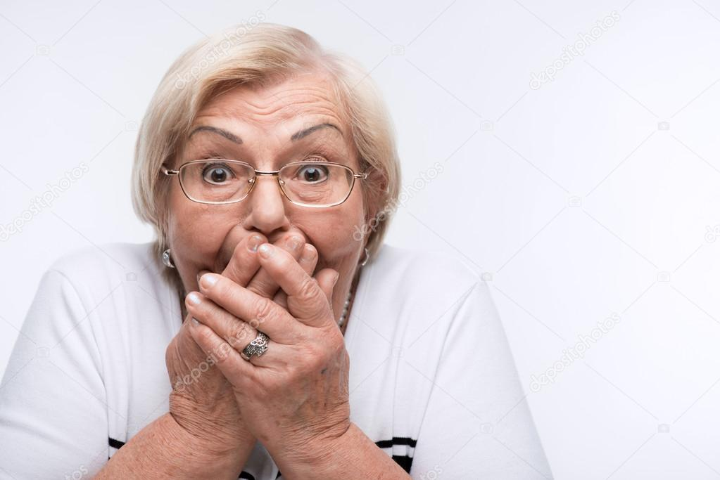 Elderly woman closes her mouth, ears and eyes with hands