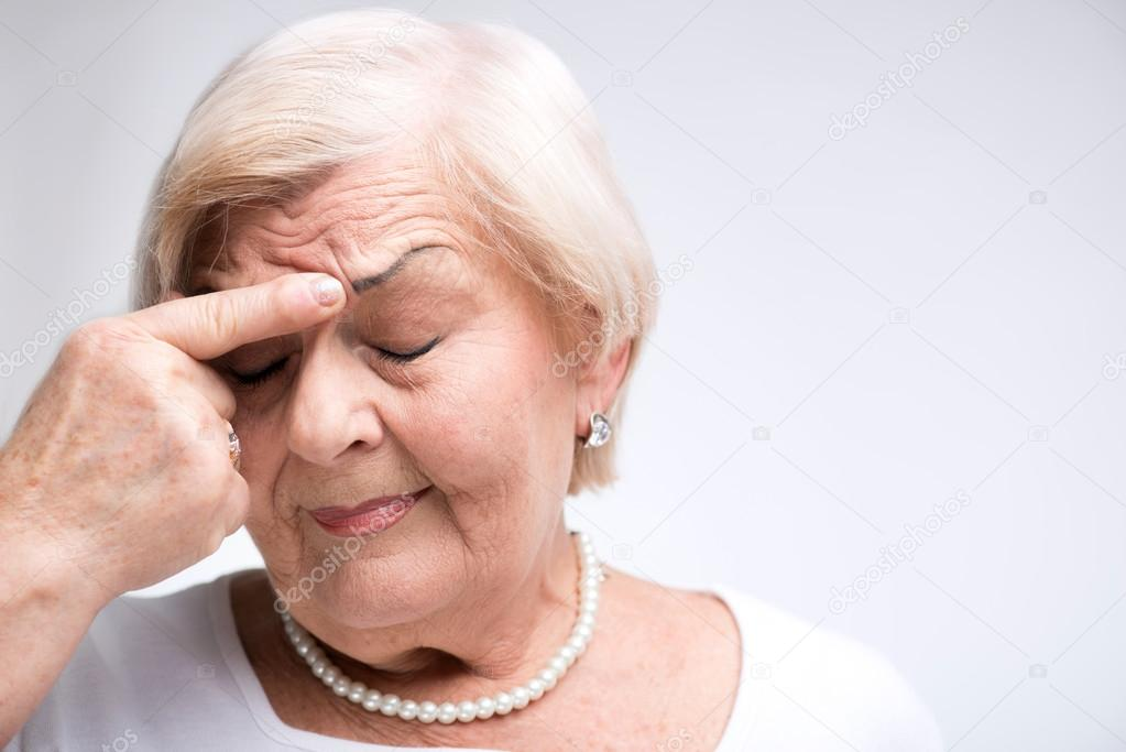Elderly lady touching her head with finger