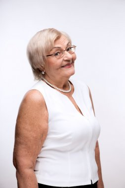 Side view portrait of a happy elegant retired woman posing in white blouse and glasses while standing against white background stock vector