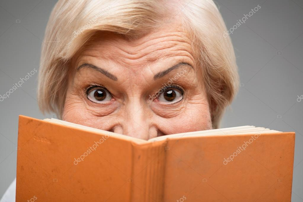 Elderly woman holding yellow book