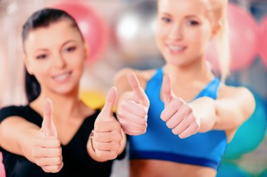 Feeling amazing after workout. Two beautiful young women in sports clothing smiling and showing their thumbs up while standing in the gym with selective focus stock vector