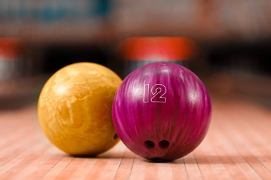 Bowling balls staying against bowling alley