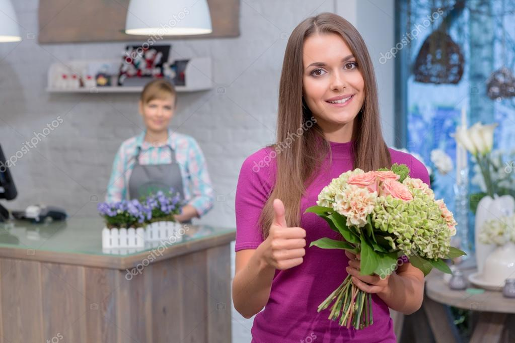 Woman with bouquet raises her thumb up