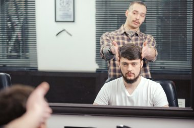 Barber discusses haircut with client