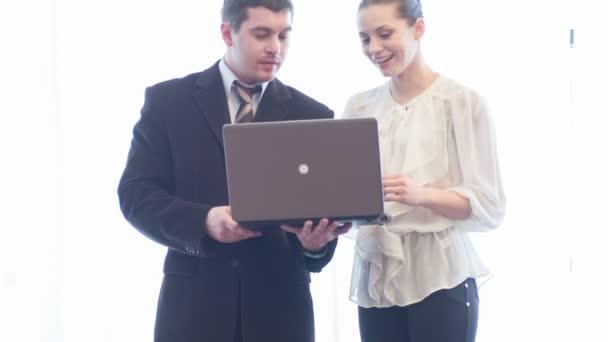 Dva usmívající se asistent pracovníci stojící s Poznámkový blok