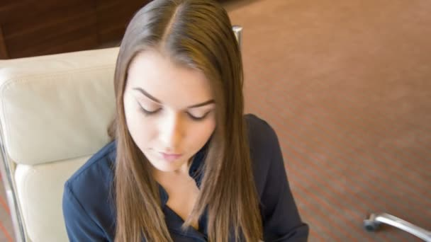 Young attractive thoughtful woman sitting at table
