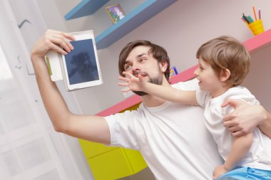Father and son use tablet