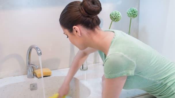 Mladá žena leštění umyvadlo
