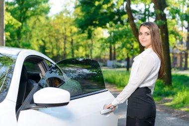 Smiling woman opening door of car