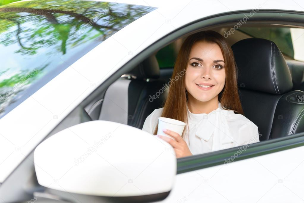 Smiling girl in car with cup of coffee