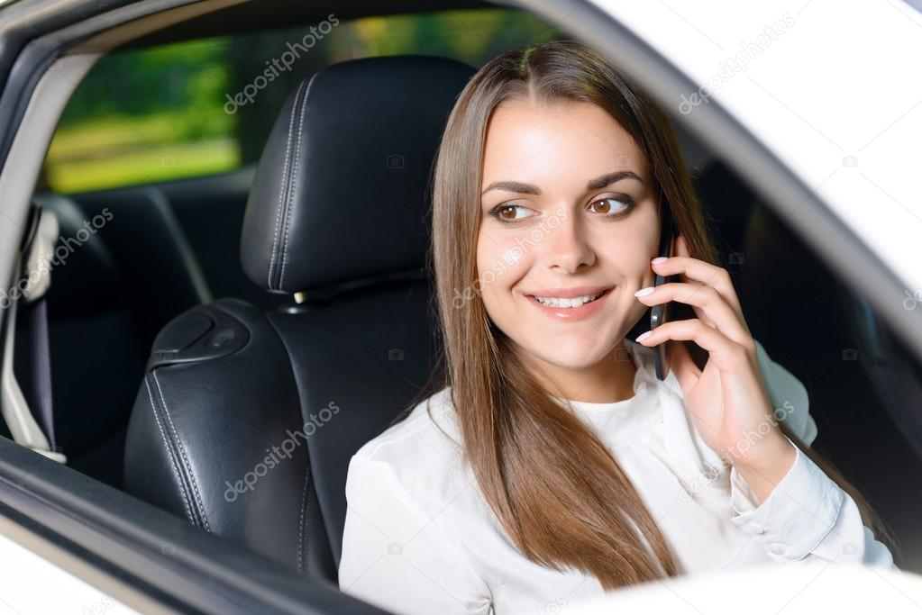 Woman using mobile phone in car
