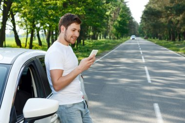 Young man using mobile phone near car