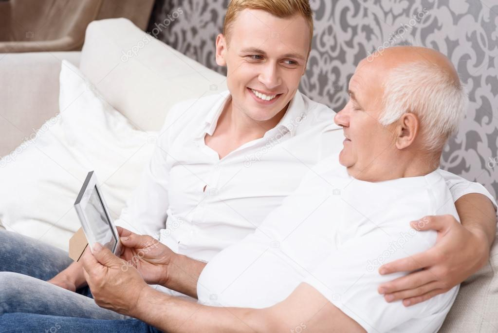 Abuelo y nieto con foto en marco — Foto de stock © Dmyrto_Z #75302355