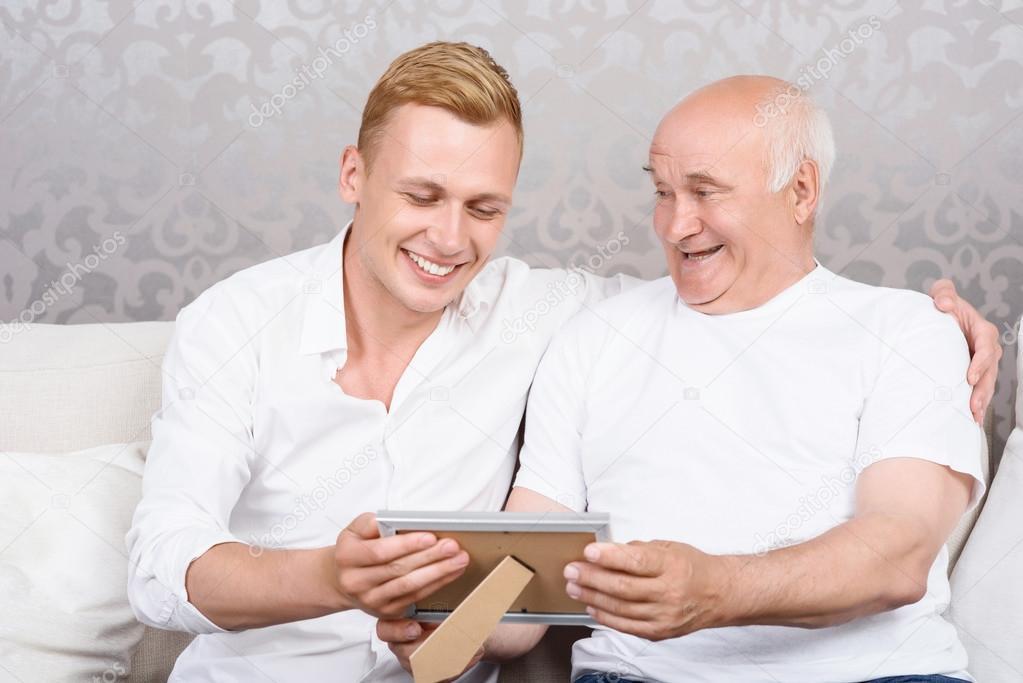Abuelo y nieto con foto en marco — Foto de stock © Dmyrto_Z #75302363