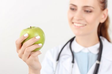 Positive doctor holding green apple