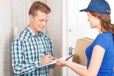 Positive deliverywoman delivering parcel
