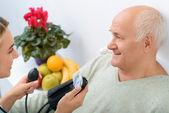 Fotografie Junge Enkelin verwendet Stethoskop Blutdruck zu überprüfen