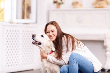 Beautiful young girl hugging her dog cheerfully.