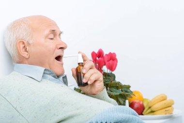 Weary senior gentleman uses his sore throat spray.