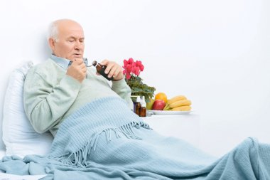 Elderly man rests in bed and pours cough syrup.