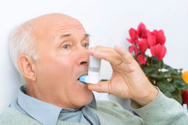 Senior aged man uses inhaler to cure his ache.