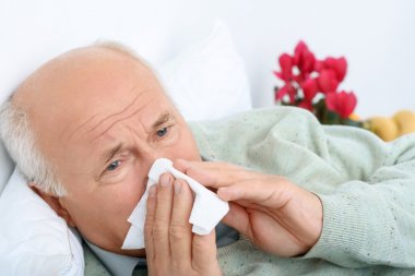 Sad exhausted old man is snorting at white handkerchief.