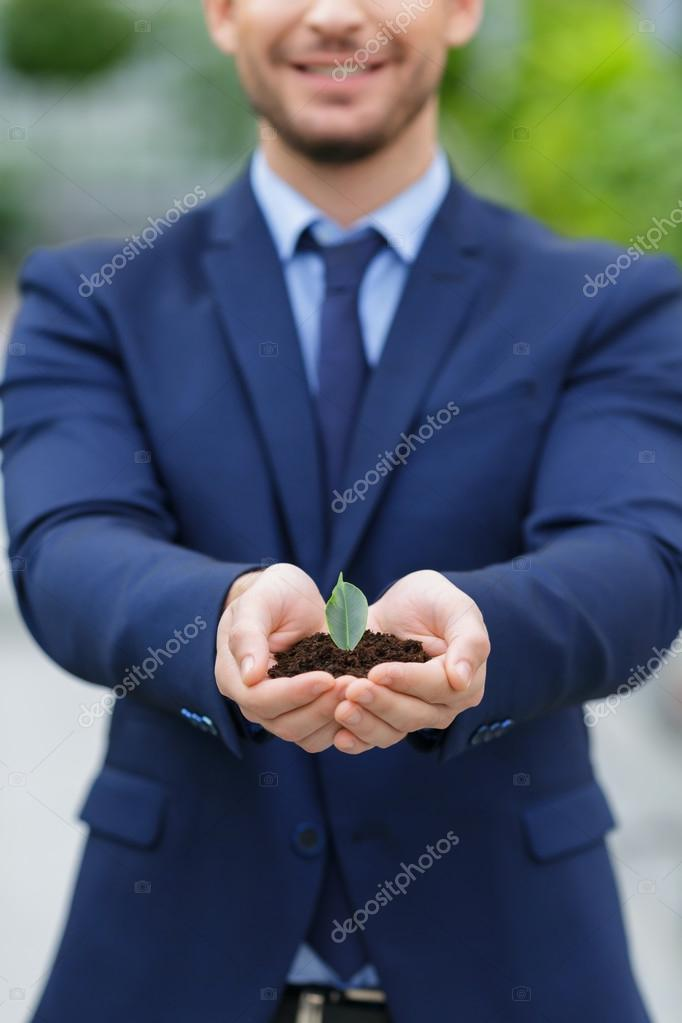Pleasant businessman holding ground in hands