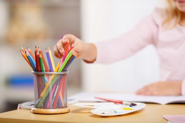 Little girl is picking colored pencils.