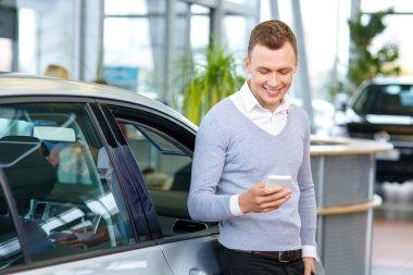 Pleasant man choosing car in auto show