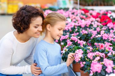 Mother and daughter are watching the flowers.
