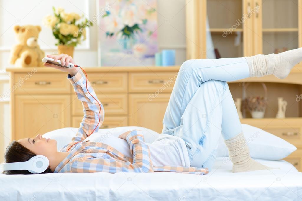Teenager Madchen Im Bett Liegend Und Musik Horen Stockfoto