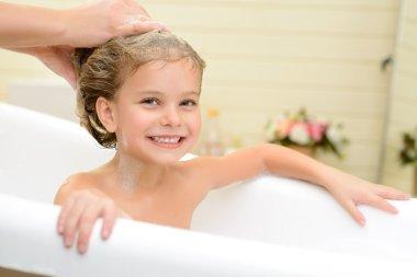 Cute little girl washing her hair