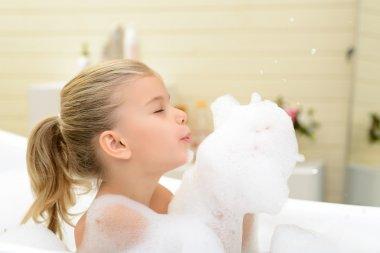 Pleasant little girl playing in bath tube